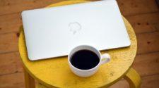 Macbook mit Kaffeetasse auf einem Hocker