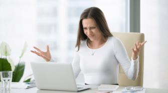 Junge Geschäftsfrau sitzt verärgert am Büroschreibtisch vor Laptop und hebt verzweifelt die Hände.