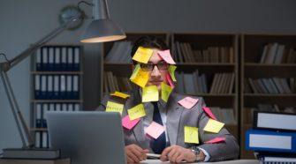 Geschäftsmann, bespickt mit Notizzetteln sitzt am Laptop spät in der Nacht