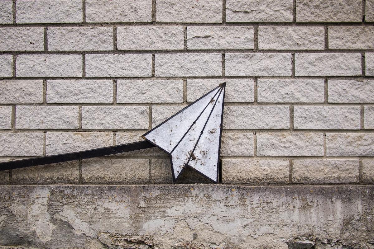 Papierflieger-Icon aus Metall lehnt an Wand