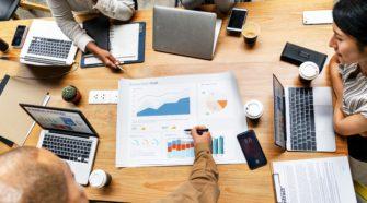 Gruppen-Meeting mit Laptops und Charts