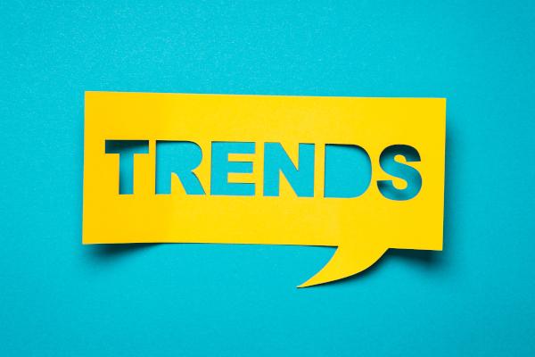 """Gelbe Sprechblase mit """"Trends"""" auf türkisem Hintergrund"""