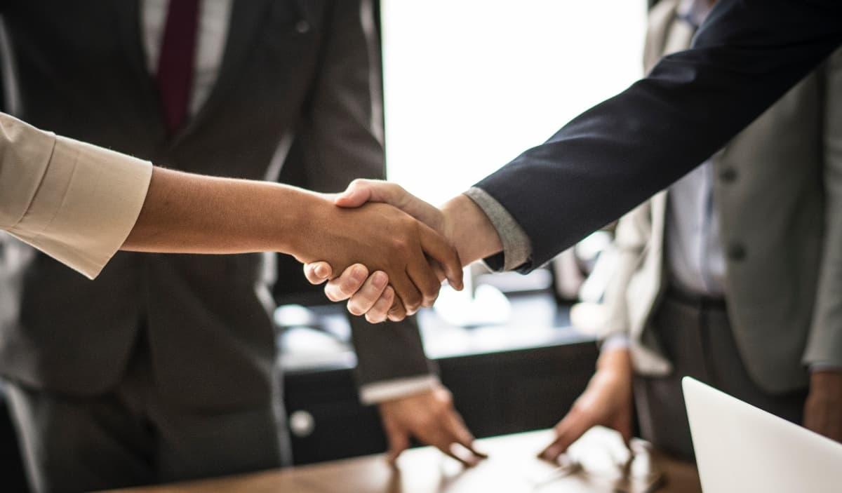 Zwei Menschen geben sich die Hand