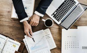 Monitoring Tools Blick auf einen Schreibtisch mit Laptop und Dokumenten
