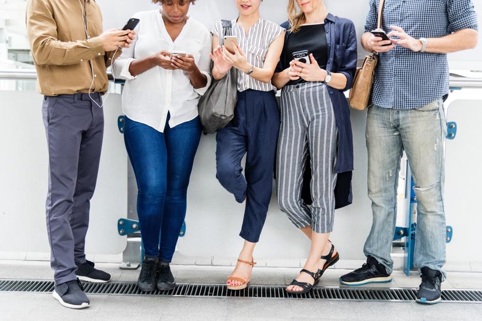 Gruppe junger Menschen lehnt an Wand und ist mit dem Smartphone beschäftigt