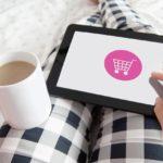 Studie zu Reimagining Commerce: Frau in karierter Hose hält Kaffee-Tasse und Tablet auf dem Schoß für Onlineshopping & Einkaufsgewohnheiten