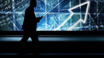 Geschäftsmann vor riesigem Monitor mit Zahlen und Grafen, die Richtung Erfolg weisen