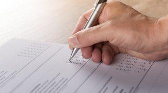 Frageborgen nach Muliple-Choice-Prinzip wird von einer Hand mit Kugelschreiber ausgefüllt