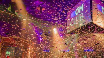 Foto zum OMClub mit feiernden Gästen und Konfetti
