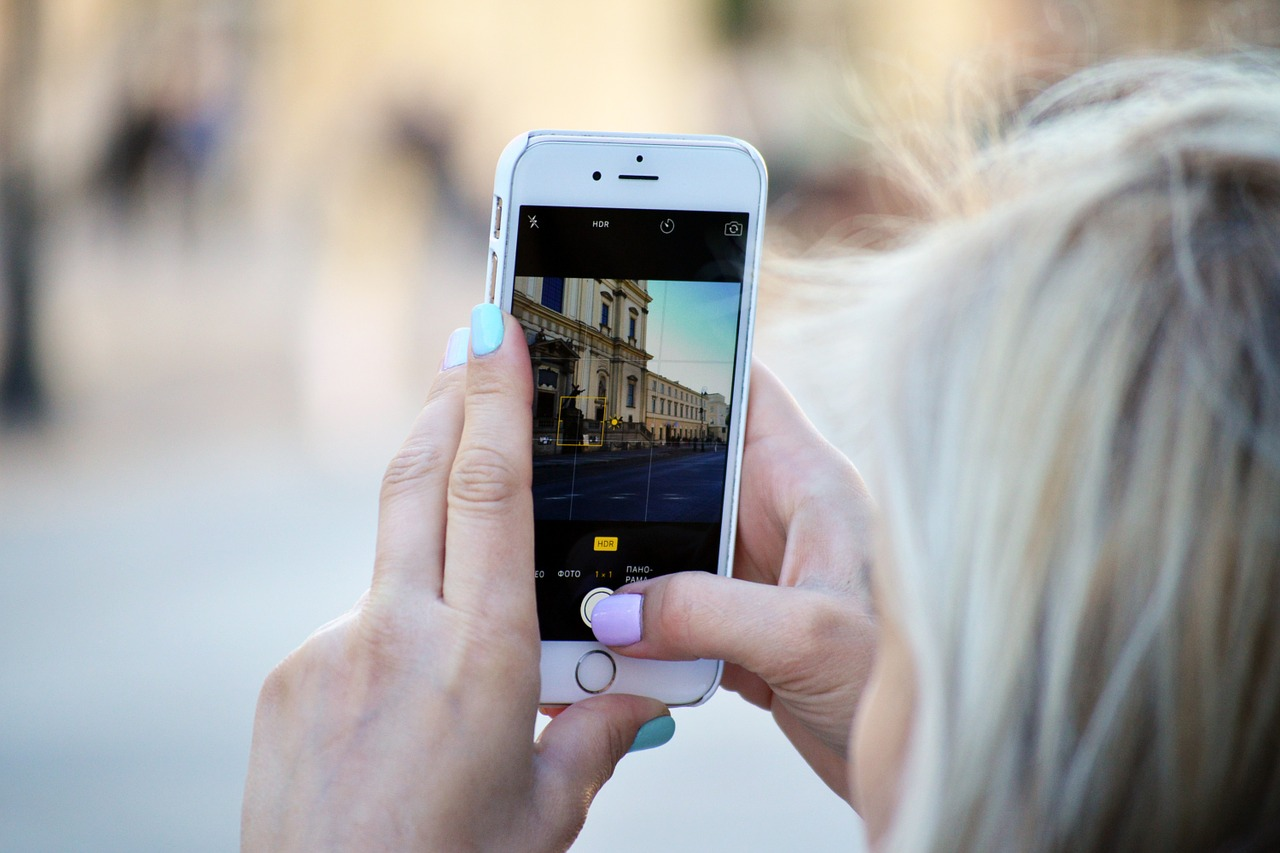 Frau mit Smartphone Fotografiert historisches Gebäude mit Instagram