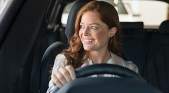 Mature beautiful woman sitting in car looking away while trying new automobile. Portrait of daydreaming mature woman doing drive test of new car. Cheerful smiling lady enjoying driving while looking away.