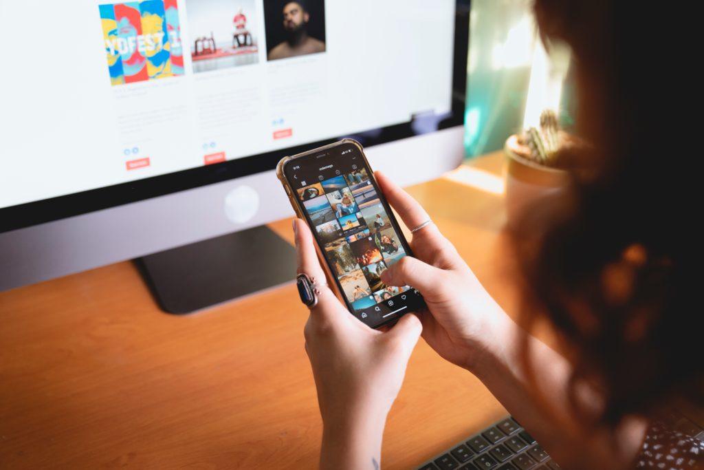 influencer finden Frau mit Handy vor Computerbildschirm